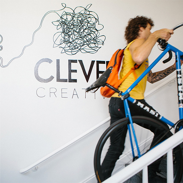 Luke, a Clever web developer walking his bike up the office front stairs