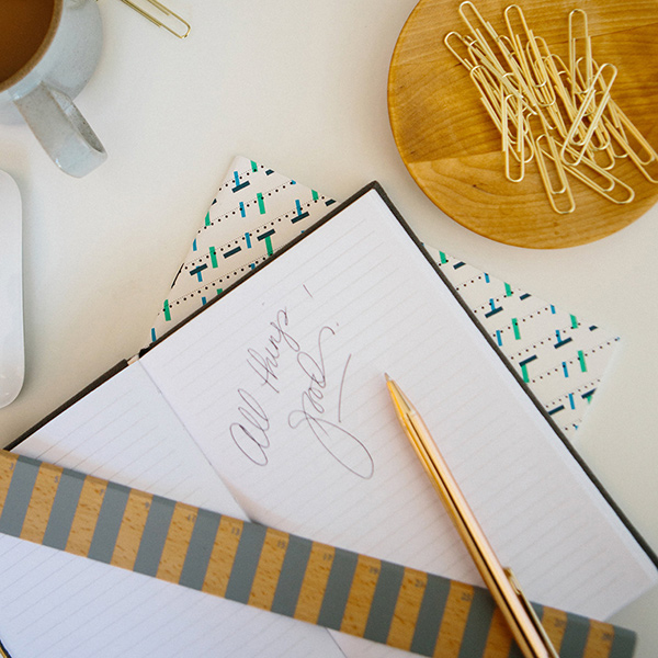 Downward photo of a notebook, gold pen, coffee cup and paperclips on a white desk.