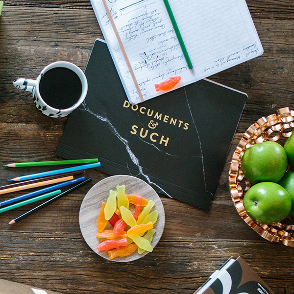 Downward photo of Clever's kitchen table with coffee, colored pencils, Swedish fish, apples and notebooks